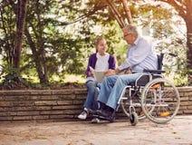 Grand-père handicapé dans le fauteuil roulant en parc dépensant le togethe de temps Images stock