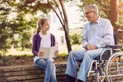 Grand-père handicapé en parc passant le temps ainsi que son gra Photographie stock