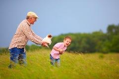 Grand-père heureux avec le petit-fils ayant l'amusement sur le champ d'été Image stock