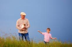 Grand-père heureux avec le petit-fils ayant l'amusement sur le champ d'été Photos libres de droits