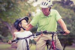 Grand-père heureux avec sa petite-fille sur leur vélo Photographie stock libre de droits