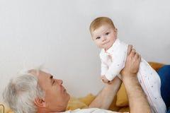 Grand-père heureux tenant l'petit-enfant adorable de bébé sur des bras Photo stock