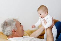 Grand-père heureux tenant l'petit-enfant adorable de bébé sur des bras Photographie stock
