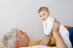 Grand-père heureux tenant l'petit-enfant adorable de bébé sur des bras Photo libre de droits
