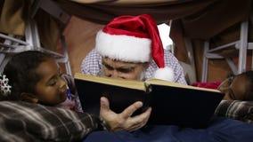 Grand-père lisant un livre à ses petite-filles banque de vidéos