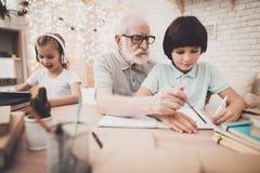 Grand-père, petit-fils et petite-fille à la maison Le grand-papa aide le garçon avec le travail photos libres de droits