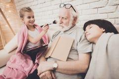 Grand-père, petit-fils et petite-fille à la maison Le grand-papa et les enfants dorment photos stock