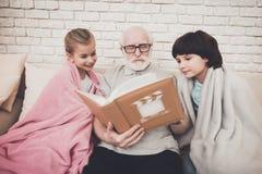 Grand-père, petit-fils et petite-fille à la maison Le grand-papa et les enfants observent des photos dans l'album photographie stock libre de droits