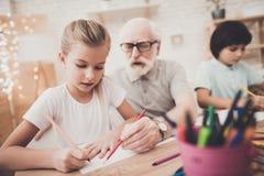 Grand-père, petit-fils et petite-fille à la maison Les enfants dessinent image libre de droits