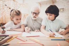 Grand-père, petit-fils et petite-fille à la maison Les enfants dessinent avec des crayons de couleur Images libres de droits