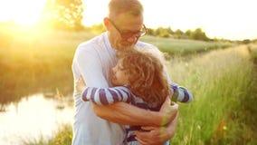 Grand-père plus âgé et petit-fils affectueux souriant et s'étreignant dehors, sur la berge Deux rétablissements banque de vidéos