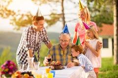 Grand-père sur l'anniversaire avec sa famille Image stock