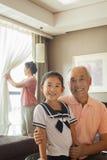 Grand-père tenant sa petite-fille, grand-mère à l'arrière-plan Photos stock