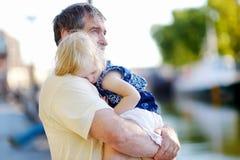 Grand-père tenant son petit petit-enfant de sommeil Photographie stock