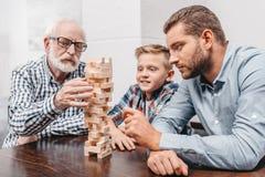 Grand-père tirant un morceau hors de la tour en bois de blocs tandis que son fils et petit-fils photos stock
