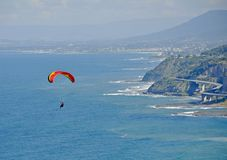 Grand Pacific Drive paragliding. Unrecognizable Paraglider in the air gliding over the Pacific ocean, Grand Pacific Drive and the Sea Cliff Bridge in the royalty free stock images