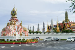 Grand palace / emerald buddha temple with elephant statue in front on the road over blue sky Royalty Free Stock Image
