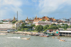Grand palace with long tail boat in Chao Phraya River in Bangkok Stock Photos