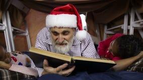 Grand-papa avec des enfants lisant des contes de fées sur Noël Ève banque de vidéos