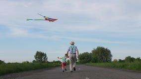 Grand-papa avec le cerf-volant de vol de petit-fils dans la campagne banque de vidéos