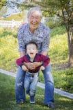 Grand-papa chinois ayant l'amusement avec son petit-fils de métis dehors photos libres de droits
