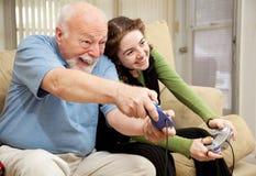 Grand-papa et jeux vidéo de l'adolescence de pièce Photos stock