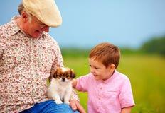 Grand-papa et petit-fils jouant avec le petit chiot, été dehors Images stock