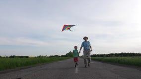 Grand-papa joyeux avec le cerf-volant de vol de petit-fils extérieur clips vidéos