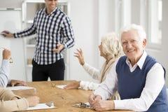 Grand-papa souriant pendant les classes informatiques photo stock