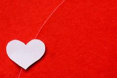 Grand papier rouge et blanc de coeur sur le fond de papier rouge Image libre de droits