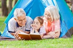 Grand-parent avec le livre de lecture de petite-fille à Photographie stock