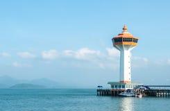 Grand phare blanc et orange avec le bateau au coin et à la mer bleue et le ciel à l'arrière-plan comme Copyspace Image libre de droits