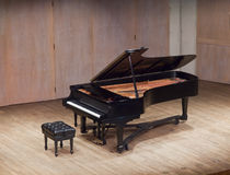 Grand piano. And bench on the concert scene Royalty Free Stock Photos