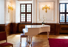 Grand piano in ballroom hall. White grand piano in Kaunas town hall, Lithuania stock images
