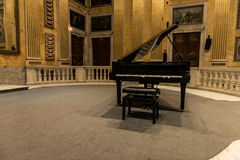 Grand Piano. A black grand piano in the middle of a music hall full of Renaissance and early Classic era painting and wall murals depicting various religious Royalty Free Stock Image