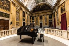 Grand Piano. A black grand piano in the middle of a music hall full of Renaissance and early Classic era painting and wall murals depicting various religious stock photos