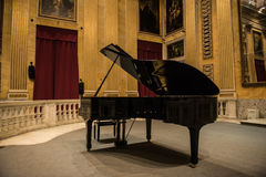 Grand Piano. A black grand piano in the middle of a music hall full of Renaissance and early Classic era painting and wall murals depicting various religious stock photo