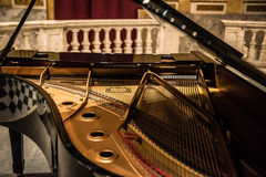 Grand Piano. A black grand piano in the middle of a music hall full of Renaissance and early Classic era painting and wall murals depicting various religious stock image