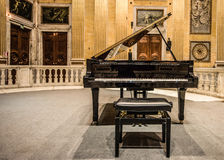 Grand Piano. A black grand piano in the middle of a music hall full of Renaissance and early Classic era painting and wall murals depicting various religious royalty free stock images