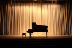 Grand piano. At concert stage with brown curtain