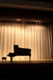 Grand piano on the curtain background Stock Photo