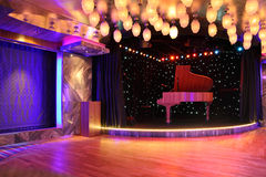 Grand piano on empty stage with many lamp Stock Images
