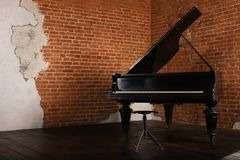 Grand piano with raised lid near brick wall. Grand piano with raised lid and stool near brick wall royalty free stock image