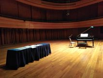 Grand piano on stage. In a concert hall, recitak, recital, rehearsal, nobody, music, musical, instrument, score, notes, university, cultural, centre, center royalty free stock photography
