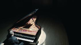 Grand piano on stage : an elegant man in a black suit playing grand piano on stage in a concert hall, aerial video