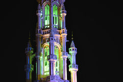 Grand Place in Brussels. Violet and green night illumination of medieval tower on Grand Place in Brussels Stock Photo
