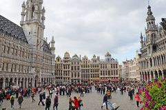 Grand Place in Brussels. Many tourists walk and look at beautiful buildings on the main square in Brussels. Flowers bloom on the Grand Place in Brussels royalty free stock images
