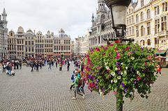 Grand Place in Brussels. Many tourists walk and look at beautiful buildings on the main square in Brussels. Flowers bloom on the Grand Place in Brussels stock photography