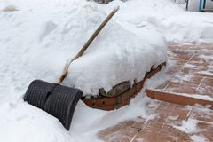 Grand plastique noir pellant avec la poignée en bois dans la neige Nettoyage de la neige après les chutes de neige lourdes des ét image stock