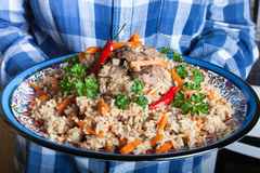 Grand plat de pilaf d'Ouzbékistan de couleur avec le poivron rouge épicé et le cilantro frais Images stock